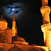 Minarets of the Sultan Ahmed Mosque (Blue Mosque) glow under moonlight in Istanbul, Turkey. Built in the early 17th Century by Ahmed I, Sultan Ahmed is a focal point for Turkish Muslims as well as tourists visiting Istanbul.