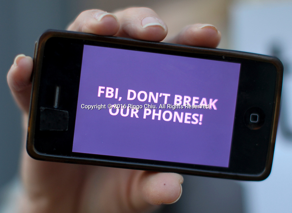 A demonstrator hold up his iPhone during a rally in support of data privacy outside the Apple store, Tuesday, Feb. 23, 2016, in Los Angeles. Protesters assembled in more than 30 cities around the world to lash out at the FBI for obtaining a court order that requires Apple to make it easier to unlock an encrypted iPhone used by a gunman in December's mass murders in California.(Photo by Ringo Chiu/PHOTOFORMULA.com)<br /> <br /> Usage Notes: This content is intended for editorial use only. For other uses, additional clearances may be required.