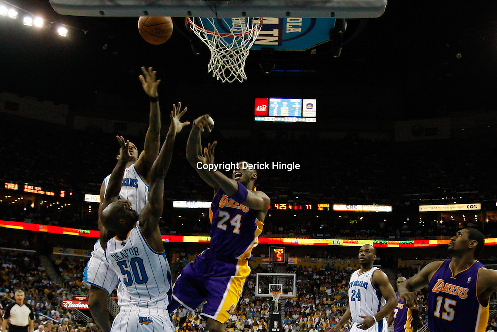 April 24, 2011; New Orleans, LA, USA; Los Angeles Lakers shooting guard Kobe Bryant (24) shoots over New Orleans Hornets center Emeka Okafor (50) and small forward Trevor Ariza (1) during the fourth quarter in game four of the first round of the 2011 NBA playoffs at the New Orleans Arena. The Hornets defeated the Lakers 93-88.   Mandatory Credit: Derick E. Hingle