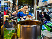 27 FEBRUARY 2019 - BANGKOK, THAILAND: A street food vender in Bangkok's Chinatown plates up a customer's order of grilled pork and rice. Bangkok, a city of about 14 million, is famous for its raucous nightlife. But Bangkok's real nightlife is seen in its markets and street stalls, many of which are open through the night.        PHOTO BY JACK KURTZ