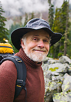 A portrait of a happy mature man out hiking in the mountains.