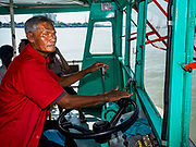 29 OCTOBER 2018 - PHRA PRADAENG, SAMUT PRAKAN, THAILAND: A man steers a cross river ferry on the Chao Phraya River in Phra Pradaeng. The Chao Phraya River is the lifeline of central Thailand. Water from the river, and its tributaries, provides domestic and agricultural water to homes and farms. It's also a major commercial artery with large ocean going freighters going up to Bangkok's Khlong Toey port.         PHOTO BY JACK KURTZ