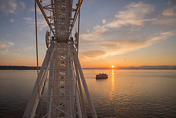 "United States, Washington, Seattle, ""Great Wheel"" ferris wheel, Elliott Bay, a ferry, and the Olympic Mountains at sunset"