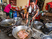 """09 AUGUST 2014 - BANGKOK, THAILAND:      A volunteer cooks chicken with basil for people waiting for free food at the Ruby Goddess Shrine in the Dusit section of Bangkok. The seventh month of the Chinese Lunar calendar is called """"Ghost Month"""" during which ghosts and spirits, including those of the deceased ancestors, come out from the lower realm. It is common for Chinese people to make merit during the month by burning """"hell money"""" and presenting food to the ghosts. At Chinese temples in Thailand, it is also customary to give food to the poorer people in the community.    PHOTO BY JACK KURTZ"""