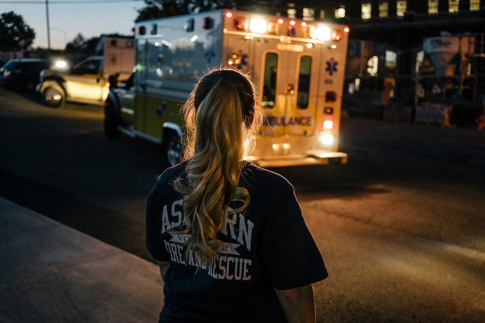 Heidi Wallner, firefighter, National Registry emergency medical technician, and safety supervisior for LSG Sky Chefs, helps direct an ambulance in Ashburn Virginia on Sept. 23, 2015. Wallner is a volunteer, working one night a week with other EMTs.