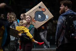 © Licensed to London News Pictures. 01/09/2019. Manchester, UK. A woman carries a child and a placard with an image of a dodo . Extinction Rebellion block roads around Deansgate in Manchester City Centre , during a third day of planned disruption organised by environmental campaigners . Manchester City Council has declared a climate emergency but activists say the council's development plans do not reflect this . Photo credit: Joel Goodman/LNP