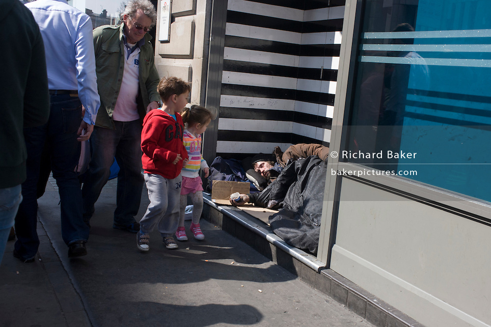 Children stare at sleeping homeless man in central London doorway.