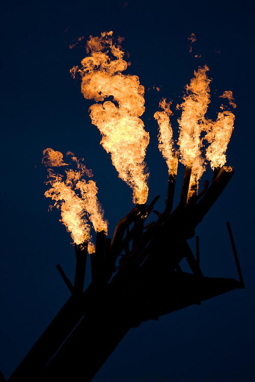USA, Alaska, Kenai Peninsula, Natural gas flare from offshore oil drilling rigs in Cook Inlet on summer evening