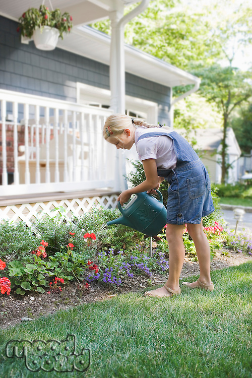 Girl (7-9) watering flowers at house back yard