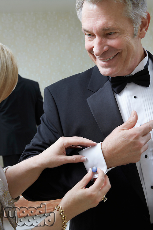 Middle-aged woman fastening husband's cufflink