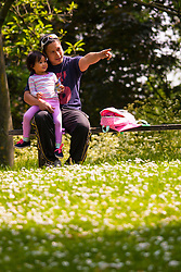 Regent's Park, London, May 17th 2014. Abril Samonte and his three-year-old daughter Gabbie take a rest amongst the wildflowers in London's Regent's Park.