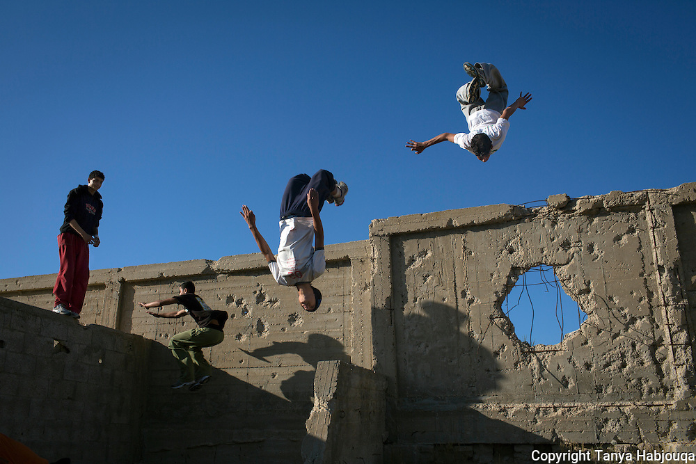 The Gaza Parkour team practices in a cemetery  on the outskirts of their refugee camp in Khan Younis, Gaza. The walls show damage from past Israeli incursions.
