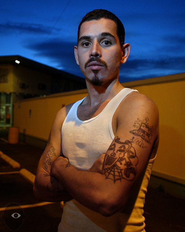 """Mark DeLeon who is with the Southside Loco Mafia Varios. He wears many tattoos including t a classic one denoting the gang philosophy of laugh now, cry later (bottom). Also a Cholo hat with his nickname """"Panther"""" and various affiliations."""