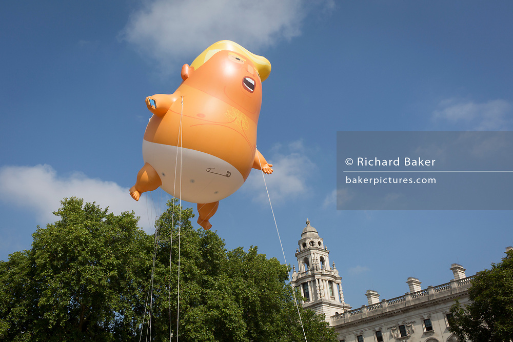 The inflatable balloon called Baby Trump flies above Parliament Square in Westminster, the seat of the UK Parliament, during the US President's visit to the UK, on 13th July 2018, in London, England. Baby Trump is a 20ft high orange blimp depicting the US President as an enraged, smartphone-clutching infant - and given special permission to appear above the capital by London Mayor Sadiq Khan because of its protest rather than artistic nature. It is the brainchild of Graphic designer Matt Bonner. (Photo by Richard Baker / In Pictures via Getty Images)