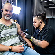 Santo Cuervo, Tattoo a client at The Great British Tattoo Show, on 26 May 2019, London, UK.