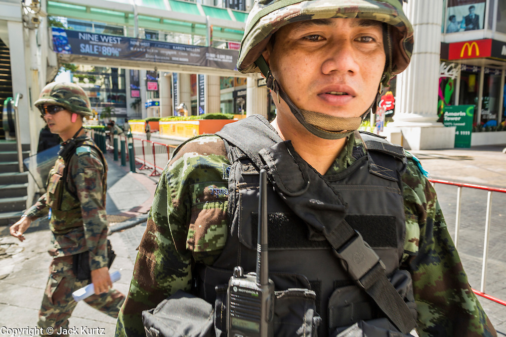 "01 JUNE 2014 - BANGKOK, THAILAND:  Thai soldiers patrol the Ratchaprasong district in Bangkok. The Thai army seized power in a coup that unseated a democratically elected government on May 22. Since then there have been sporadic protests against the coup. The protests Sunday were the largest in several days and seemed to be spontaneous ""flash mobs"" that appeared at shopping centers in Bangkok and then broke up when soldiers arrived. Protest against the coup is illegal and the junta has threatened to arrest anyone who protests the coup. There was a massive security operation in Bangkok Sunday that shut down several shopping areas to prevent the protests but protestors went to malls that had no military presence.    PHOTO BY JACK KURTZ"