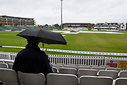 Rain Stops Play - A spectator in the Somerset Pavilion stand with an umbrella up  looks out over the covered outfield as the rain continues to fall during the Specsavers County Champ Div 1 match between Somerset County Cricket Club and Essex County Cricket Club at the Cooper Associates County Ground, Taunton, United Kingdom on 23 September 2019.