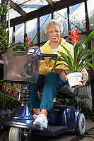 Senior woman on motor scooter in garden center