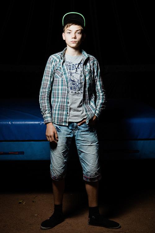 Ilya Rudenko. Ich heiße Ilya, bin vierzehn Jahre alt und komme aus Horliwka (Gorlowka), Oblast Donetsk. Mit meiner Großmutter lebe ich seit 8 Monaten in Charkiw. Wir sind in einem Studentenwohnheim untergekommen in einem Zimmer, das so groß ist wie eine Turnmatte.  Wir müssen uns Toilette und Dusche mit der ganzen Etage teilen, das ist nicht schön. Meine drei älteren Brüder Danyla, Sascha und Kiril sind noch in Horliwka. Es war nicht meine Entscheidung, meine Heimat zu verlassen, und ich wäre gerne dort geblieben. Aber als die Kämpfe immer schlimmer wurden, handelte meine Oma kurzentschlossen und floh mit mir. Ich hoffe sehr, dass wir in einem halben Jahr zurückkehren können. Wir haben zwar den Plan, aber nichts ist sicher, denn Zuhause wird immer wieder geschossen, mit Granaten und schwerer Artillerie. Horliwka stand lange unter der Kontrolle des Separatistenführers Igor Strelkow. Beide Seiten setzten in den Kämpfen Grad Raketen und schwere Artillerie ein. Das Flüchtlingswerk der vereinten Nationen geht nach Informationenen des Ukrainischen Sozialministeriums von 1.357918 registirierten Binnenflüchtlingen aus. Die Statistik erfasst jedoch nicht jene, die in den Gebieten leben, die von den prorussischen Separatisten kontrolliert werden. 13 Prozent der ukrainischen Binnenflüchtlinge (IDPs) sind Kinder. Die Hilsoganisation Vostok SOS Schätzt die Zahl der ukrainischen Binnenflüchtlinge auf ca. 2 Millionen. Wer kein Kindergeld oder andere Versorgungsleistungen des States in Anspruch nehmen kann, lässt sich nicht registrieren. Qullen: http://vostok-sos.org // http://reliefweb.int/sites/reliefweb.int/files/resources/gpc_factsheet_june_2015_en_0.pdf
