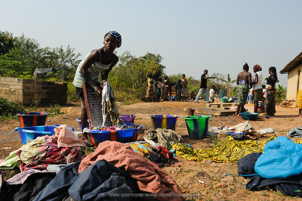 A young woman doing the family's laundry at their home in Koidu town in the Kono District of eastern Sierra Leone.