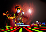 Young man uses airbrush in glowing studio.Black light