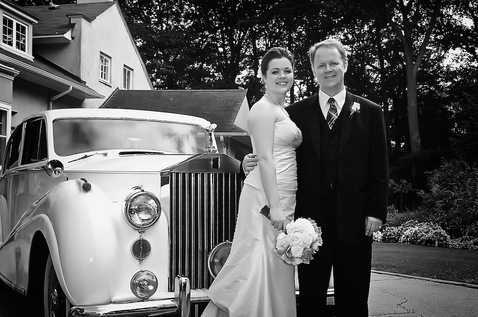 Father and his newlywed daughter pose for a photograph next to a vintage 1951 Rolls Royce.