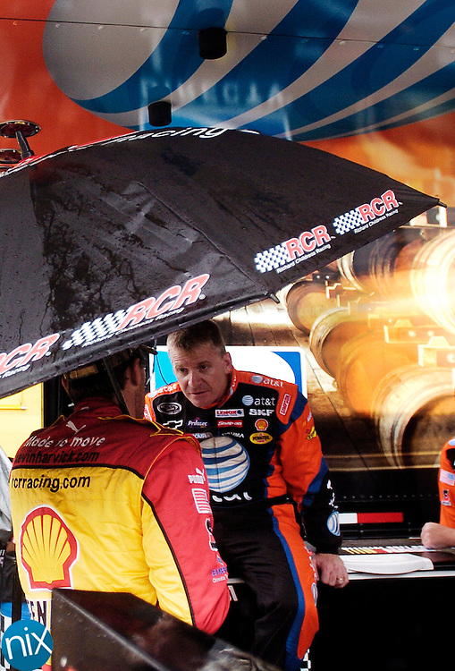 NASCAR Sprint Cup Drivers Kevin Harvick and Jeff Burton talk underneath an umbrella during as rain delayed practice at Lowe's Motor Speedway Thursday afternoon.
