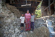 Parvita, aged 50, stands with her grandsons amongst the ruins of her home, which was destroyed in the earthquake that struck Nepal on 25 April 2015. Almost every building in every village of the rural Sindhupalchowk district, about 50 miles from Kathmandu, has sustained damage.<br /> <br /> UK aid shelter kits are being distributed to thousands of people who have lost their homes in remote parts of Nepal. Working with NGOs including MedAir, ACTED and Shelterbox, the kits are being distributed by helicopter, road and ultimately, heads, as they are carried up steep mountain trails to where they are needed.<br /> <br /> Pictures: Russell Watkins/DFID