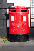 Large red traditional Royal Mail pillar box with two letter box openings, Royal Wootton Bassett, Wiltshire, England, UK