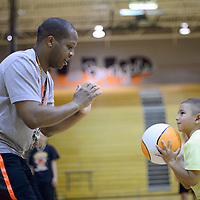 060314       Cayla Nimmo<br /> <br /> Coach Kamau Turner teaches Triniead Salas how to properly stand with the ball during basketball camp at Gallup High School Tuesday morning.