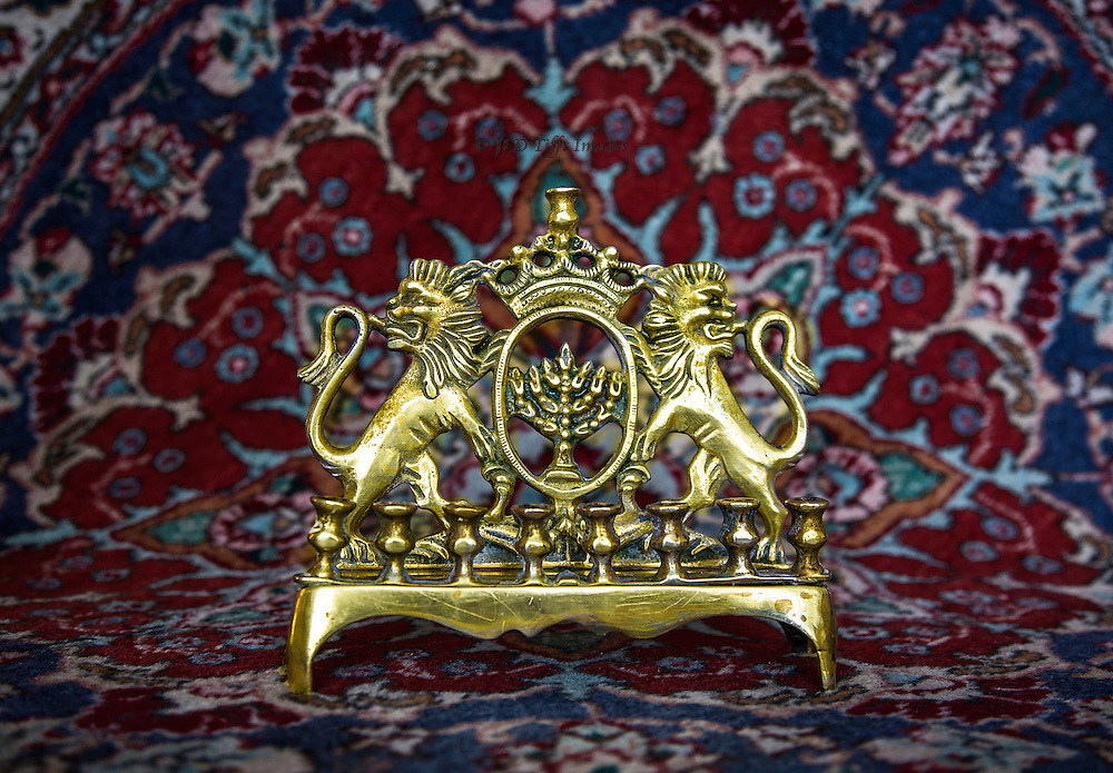 Antique brass menorah set against an oriental carpet