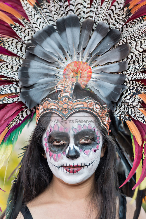 A young woman dressed as an Aztec skeleton during the Day of the Dead festival in the Plaza Civica October 27, 2016 in San Miguel de Allende, Guanajuato, Mexico. The week-long celebration is a time when Mexicans welcome the dead back to earth for a visit and celebrate life.