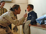 Tech. Sgt Michelle DuLac, prompts an Iraqi boy to open wide and say &quot;AHH,&quot; while at the Radhwaniya Medical Clinic Outreach Program. Tech. Sgt. DuLac is deployed to the 447th Expeditionary Medical Squadron, Sather Air Base, on Baghdad International Airport, Iraq. She is from the 1st Medical Operations Squadron, Langley Air Force Base, Va., and is a native of Fort Walton Beach, Fla.. Three times a week 1300-1600 hrs, volunteers from a combination of U.S. and Iraqi Forces, Civil Medical Outreach Center contract employees meet at the facility on the edge of the Baghdad International Airport area. Opened to support the medical needs of civilian residents, it is also a safe place for children to have fun in the playground outside the building, and receive donated school supplies and toys. The program began in September 30, 2005 by Special Forces and the 48th Brigade Combat Team from Georgia National Guard.  Since then others have continued the fully volunteer operation that has seen more than 1,500 patients.  (U.S. Air Force photo by Master Sgt. Lance Cheung)<br />