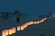 Friends and family walk along a candle vigil marking the 10th anniversary of the TWA Flight 800 disaster at Smith Point Park in Shirley, New York, Monday 17 July 2006