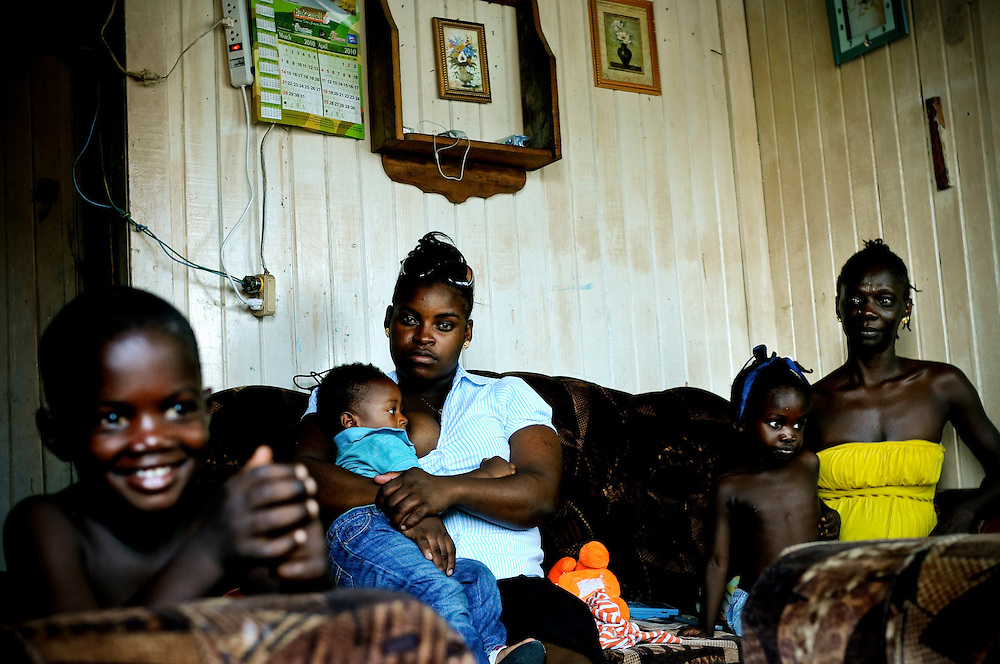 (third from left) Madonna Showe, 20, and Natasha Mansfield, 33, (right) are both single, unemployed mothers living in a ramshackle wood plank house with three other single mothers and their children in Albouystown, a ghetto in Georgetown, the capital of Guyana. Mansfield hasn't been able to find work after losing her job in a beauty salon, and says the suffering Guyanese economy means there is less work, making it harder for her to support her three children. Government plans to pave the 350 mile road from Georgetown to its southern border are expected to open Guyana to booming trade with neighboring Brazil, stimulate the economy and create more jobs.