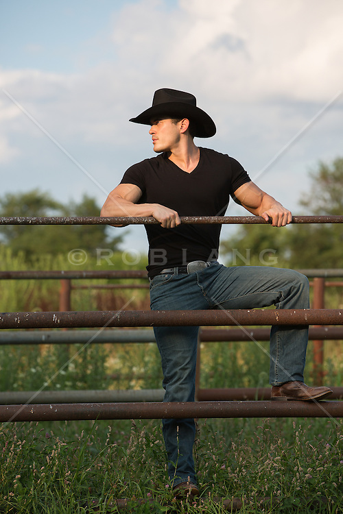 sexy cowboy on a metal fence