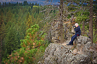 Jim Lyon, public information officer for Kootenai County Fire & Rescue, sits on a rocky point over Fifth Canyon at Q'emiln Park in Post Falls, Idaho as he photographs rescue training Monday, Sept. 20, 2010.