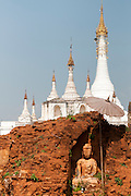Seated Buddha Statue amongst white buddhist pagodas near Shwe Inn Thein Pagoda, Inle Lake, Shan State.