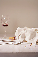 Wine glass cutlery dish cloth on messy table