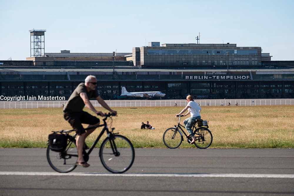 Cyclists on runway at former Tempelhof Airport now public park  in Kreuzberg, Berlin, Germany