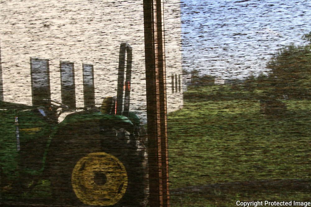 A tractor seen through a screen window in Iowa appears to be  painting.