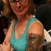 Kristine Lin from Lake Worth, Florida has a dinosaur theme tattoo by ink artist Trevor Wilson of West Palm Beach, Fla. at the 18th Annual South Florida Tattoo Expo<br /> Photography by Jose More