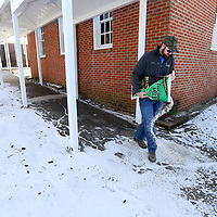 Ian Reed, a Tupelo Public School District Maintenance Department employee, spreads salt on the sidewalks inside the walkways at Lawhon Elementary School on Wednesday morning. All the Tupelo Public School District schools were treated for icy walkways in preparation for the possibility of students returning to school on Thursday.