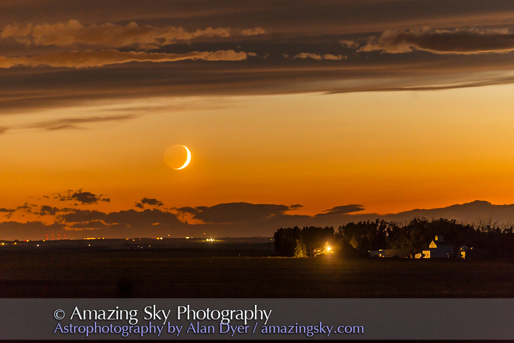 The waxing crescent Moon setting over a nearby farm, on June 26, 2017. Shot at the start of a time-lapse sequence, and shot in haste from home as the Moon appeared from beneath an otherwise very cloudy sky. The dark side of the Moon is lit by Earthshine, prominent despite the Moon&rsquo;s low altitude and bright twilight sky.<br /> <br /> With the 200mm lens.