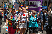 "New York, NY - 25 June 2017. New York City Heritage of Pride March filled Fifth Avenue for hours with groups from the LGBT community and it's supporters. A young woman with a T-shirt reading ""I [heart] my moms"" marching with both her moms, one of whom carries a sign reading ""resist the war against women."""
