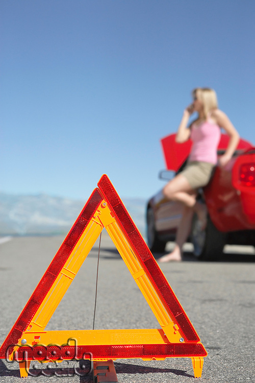 Warning triangle in front of woman on cell phone by red sports car