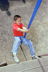Young boy swinging on metal pole in children's playground,