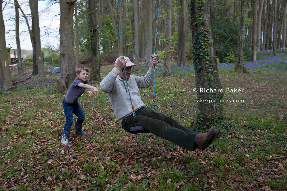 A 7 year-old boy pushes his 75 year-old granddad on a swing in local woods, on 23rd April 2017, in Wrington, North Somerset, England.