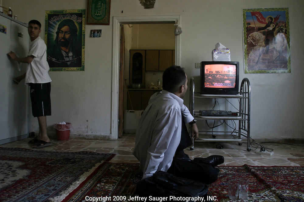 Emad Al-kasid, center, watches the first official meeting of Iraq's new government in his father's apartment in the Iraqi area of Damascus, Syria, Sunday, July 13, 2003. His brother Sagid, 17, is at left. Al-kasid has been planning has been planning the trip home to Nasiriyah, Iraq, over the last year. He is visiting his immediate family is in Damascus, Syria, as hundreds of thousands of Iraqi Shiite settled in Syria after the Gulf War and their uprising against Saddam Hussein in 1991.