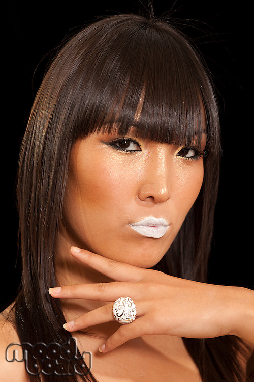 Portrait of beautiful young woman wearing ring with white lipstick
